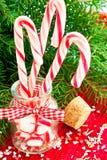 Ajunte bastões de doces listrados no frasco de vidro no fundo do Natal Fotografia de Stock Royalty Free