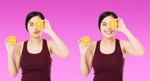 Ajustado mulher coreana, asiática que guarda partes de laranjas isoladas no fundo roxo, conceito cosmético dos cuidados com a pel foto de stock