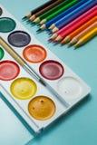 Ajustado para tirar: pinturas da aquarela e lápis coloridos em um fundo azul fotos de stock royalty free