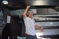 Ajustador da vela e timoneiro Maciel Cicchetti abaixo das plataformas em Team Vestas Wind Foto de Stock