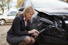 Ajustador de pérdida con la tableta de Digitaces que examina el coche dañado imagen de archivo libre de regalías