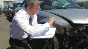Ajustador de pérdida que examina el coche implicado en accidente almacen de video