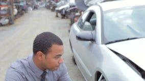Ajustador de pérdida que examina la ruina del coche usando la tableta de Digitaces metrajes