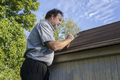 Ajustador de seguro que figura dano da saraiva ao telhado imagens de stock