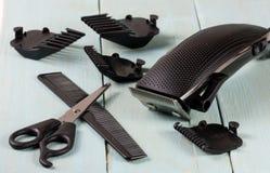 Ajustador do cabelo com pente e tesouras no fundo de madeira foto de stock
