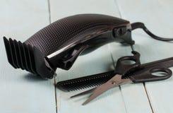Ajustador do cabelo com pente e tesouras no fundo de madeira imagens de stock