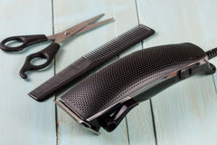 Ajustador do cabelo com pente e tesouras no fundo de madeira fotos de stock royalty free