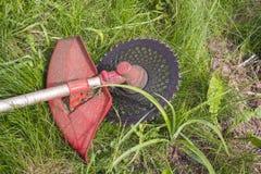 Ajustador para cortar a grama após o trabalho que encontra-se na terra fotografia de stock royalty free