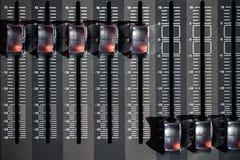 Ajustadores do od da vista superior e botões vermelhos de um console de mistura É usado para que as alterações dos sinais audio c Fotos de Stock