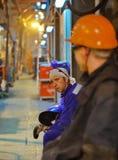 Ajustadores y soldadores de los trabajadores en ropa protectora y un casco Trabajo en las instalaciones industriales del funciona Fotos de archivo libres de regalías