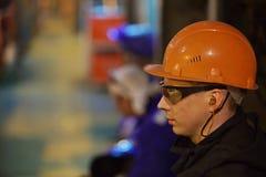 Ajustadores y soldadores de los trabajadores en ropa protectora y un casco Trabajo en las instalaciones industriales del funciona Imagen de archivo