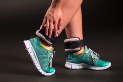 Ajustando pesos do tornozelo Foto de Stock