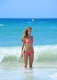 Ajuste atractivo y mujer joven bronceada que son salpicados por una onda Imagen de archivo