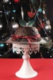 Ajuste bonito da tabela do Natal na frente da árvore de Natal, caracterizando um pudim de ameixa clássico Imagem de Stock Royalty Free