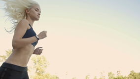 Ajuste bonito e estrada loura saudável da mulher que correm com perseguidor da aptidão vídeos de arquivo