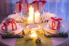 Ajuste cambiante de la tabla de la Navidad con los regalos para la Nochebuena Foto de archivo libre de regalías