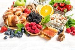 Ajuste con los cruasanes, muesli, bayas frescas de la mesa de desayuno Imagen de archivo libre de regalías