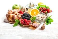 Ajuste con los cruasanes, muesli, bayas frescas de la mesa de desayuno Foto de archivo libre de regalías