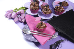 Ajuste cor-de-rosa e roxo do dia de graduação do partido da tabela com queques Fotografia de Stock