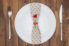Ajuste, cuchillo, bifurcación, servilleta y placa de la cena del día de tarjeta del día de San Valentín Foto de archivo