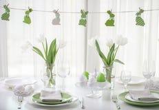 Ajuste da decoração e da tabela da tabela da Páscoa com tulipas brancas e pratos da cor verde e branca Decoração da Páscoa sob a  fotografia de stock