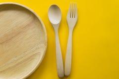 Ajuste da forquilha, da colher e da madeira do prato com fundo amarelo fotos de stock royalty free