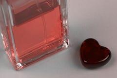 Ajuste da garrafa e do coração do parfume como um símbolo do presente com amor fotos de stock