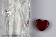 Ajuste da garrafa e do coração do parfume como um símbolo do presente com amor imagens de stock