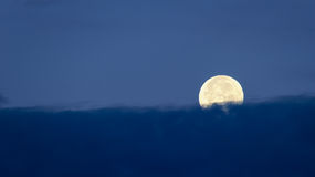 Ajuste da Lua cheia atrás das nuvens Fotografia de Stock Royalty Free