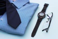 Ajuste da roupa e dos acessórios para o homem no fundo azul imagem de stock royalty free