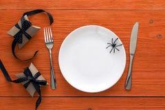 Ajuste da tabela de Dia das Bruxas com cutelaria, caixas de presente e decorativo Foto de Stock