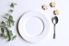 Ajuste da tabela do ano novo ou do Natal com placa, e uma colher, um eucalipto e uns doces festivos caseiros Party a decoração imagem de stock royalty free