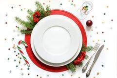 Ajuste da tabela do Natal com dishware branco, pratas e as decorações vermelhas no fundo branco Vista superior imagem de stock