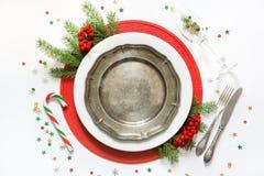 Ajuste da tabela do Natal com dishware do vintage, pratas e as decorações vermelhas no fundo branco Vista superior fotos de stock