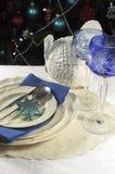 Ajuste da tabela do Natal na frente da árvore de Natal, com vidros de cristal do cálice do vinho do tema azul - vertical Fotografia de Stock Royalty Free