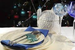 Ajuste da tabela do Natal na frente da árvore de Natal, com vidros de cristal do cálice do vinho do tema azul Fotos de Stock