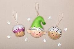 Ajuste das decorações da árvore de Natal, bolo, duende, cookies, feitos a mão do feltro de um fundo bege com flocos de neve ilustração do vetor