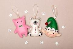 Ajuste das decorações da árvore de Natal, urso leitão, polar, duende, feito a mão do feltro em um fundo bege com flocos de neve ilustração stock