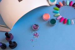 Ajuste das ferramentas cosméticas para o tratamento de mãos e o pedicure em um fundo azul imagens de stock royalty free