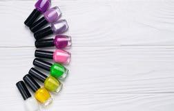Ajuste das garrafas do verniz para as unhas na cor diferente no fundo de madeira branco foto de stock