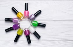 Ajuste das garrafas do verniz para as unhas na cor diferente no fundo de madeira branco imagem de stock royalty free