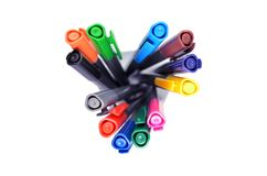 Ajuste das penas multi-coloridas que estão em um vidro transparente, vista superior no fundo branco, orientado horysontally foto de stock