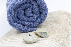 Ajuste das toalhas de banho com flores secadas e as pedras azuis do mar imagens de stock