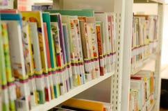 Ajuste de la biblioteca con los libros y el material de lectura en estante Fotos de archivo