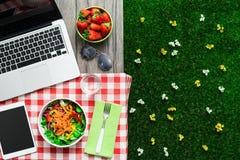 Ajuste de la comida campestre con el ordenador portátil foto de archivo libre de regalías