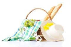 Ajuste de la comida campestre con el vino, las frutas y el sombrero del verano aislado en blanco Foto de archivo