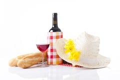 Ajuste de la comida campestre con el vino, las frutas y el sombrero del verano aislado en blanco Fotografía de archivo libre de regalías