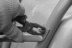 Ajuste de la nuez con los alicates en la mano Imagen de archivo libre de regalías