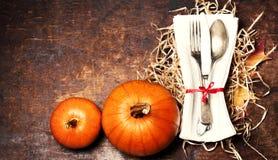 Ajuste de la tabla de la acción de gracias con la calabaza anaranjada Cubiertos estacionales Imagenes de archivo