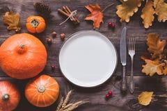 Ajuste de la tabla de la acción de gracias del otoño con la placa, los cubiertos y las calabazas vacíos foto de archivo libre de regalías